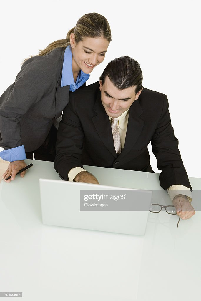 Businessman and a businesswoman using a laptop and smiling : Foto de stock