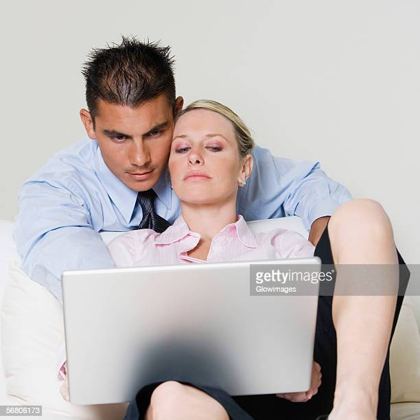 businessman and a businesswoman using a laptop - bending over in skirt stock pictures, royalty-free photos & images