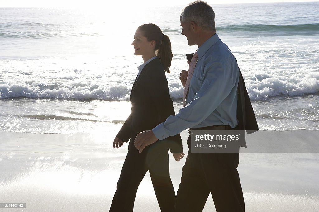 Businessman and a Businesswoman Walking at the Water's Edge on a Beach : Stock Photo