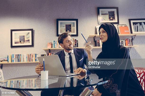 Businessman and Arab Colleague working together to complete assignment