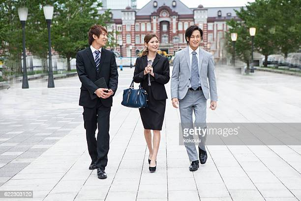 Businessman and business woman are walking while talking