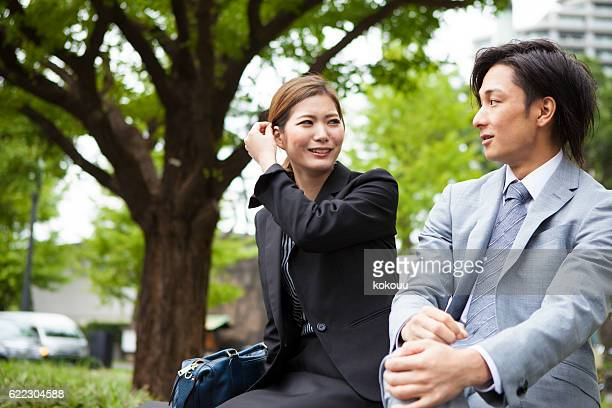 Businessman and business woman dating in the park