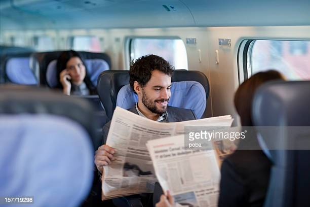 Businessman and business woman  reading  Newspaper  on a Train