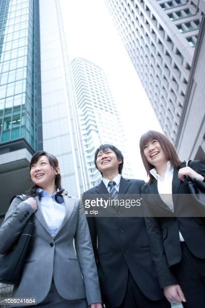ビル街に立つビジネスマンとビジネスウーマン - ルーキー ストックフォトと画像