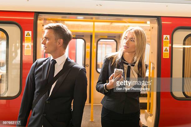 businessman and businesswoman alighting train, london underground, uk - vertical red tube fotografías e imágenes de stock