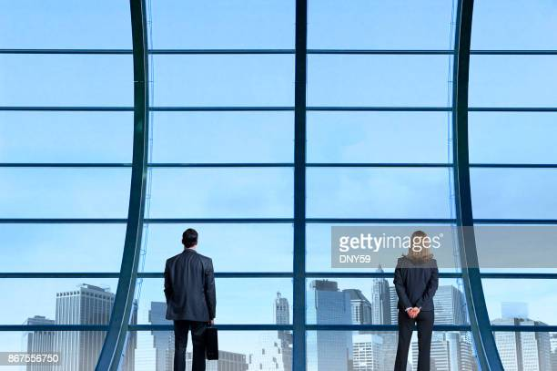 Businessman And Businesswoman Apart From One Another Looking Through Window At Distant Skyline