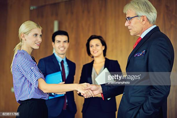 Businessman and businesswoman are shaking their hands