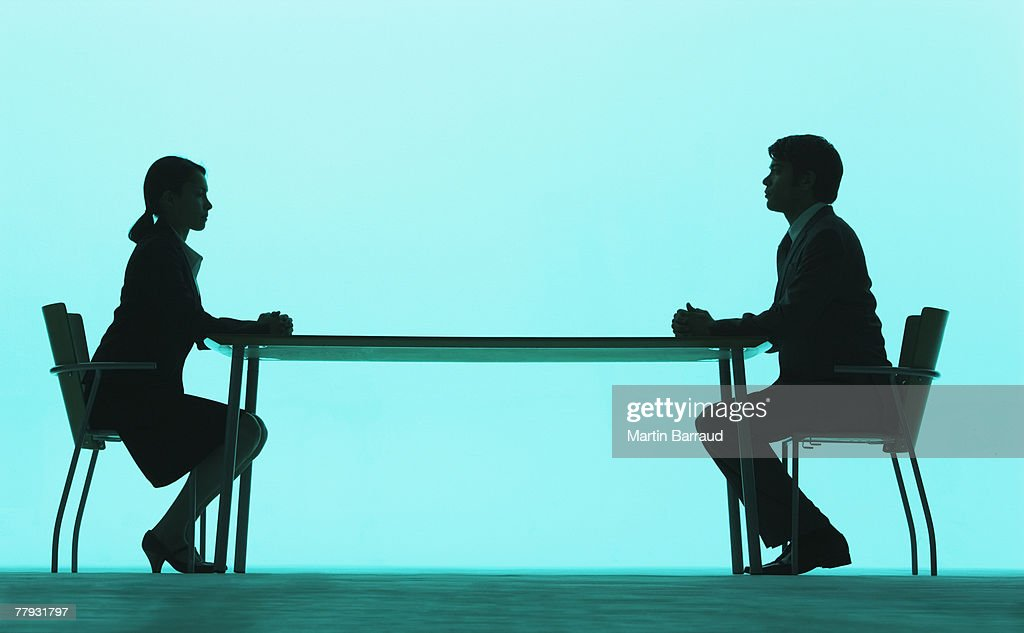 Businessman and businesswoman at a table : Stock Photo