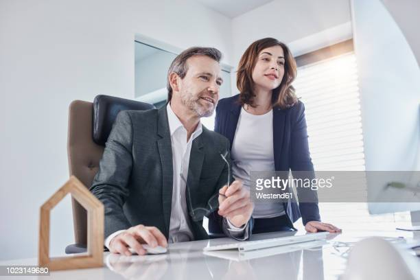 Businessman and businesswoman at desk in office with architectural model