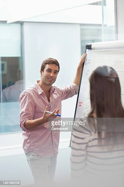Businessman and businesswoman brainstorming at flipchart
