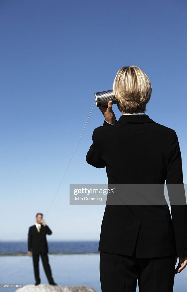 Businessman and Businesswoman Communicate With Each Other With Cans and a String : Stock Photo
