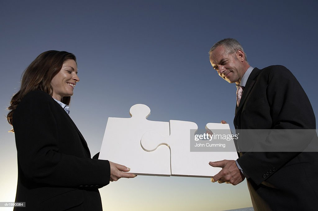 Businessman and Businesswoman Connect Two Large Jigsaw Pieces : Stock Photo