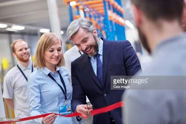Businessman and businesswoman cutting ceremonial ribbon in fiber optics factory
