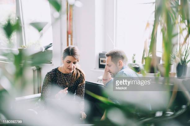 businessman and businesswoman discussing in creative office - design studio stock pictures, royalty-free photos & images