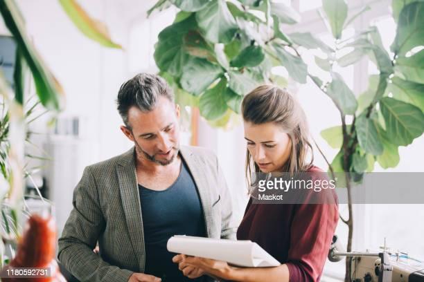 businessman and businesswoman discussing over note pad in creative office - hell beleuchtet stock-fotos und bilder