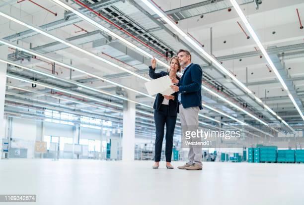 businessman and businesswoman discussing plan in a factory hall - halle gebäude stock-fotos und bilder