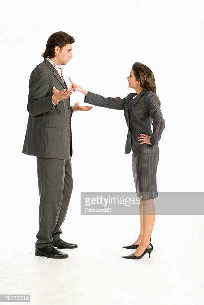 Businessman and businesswoman arguing at each other, side view
