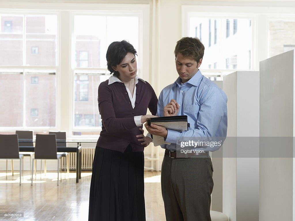 Businessman and Businesswoman Examining a Document in a Folder : Stock Photo
