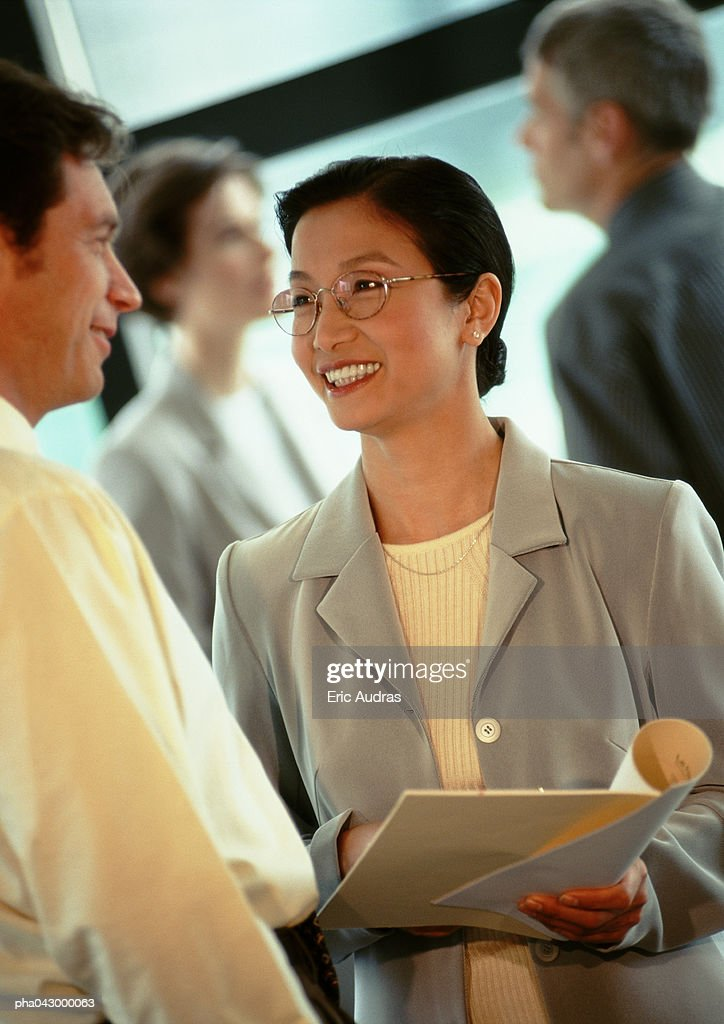 Businessman and businesswoman face to face, focus on businesswoman smiling : Stockfoto