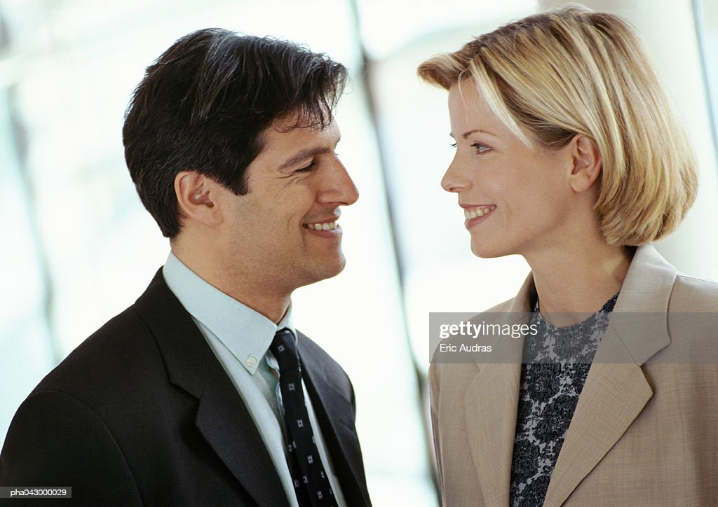 Businessman and businesswoman face to face, smiling, close-up : Stockfoto