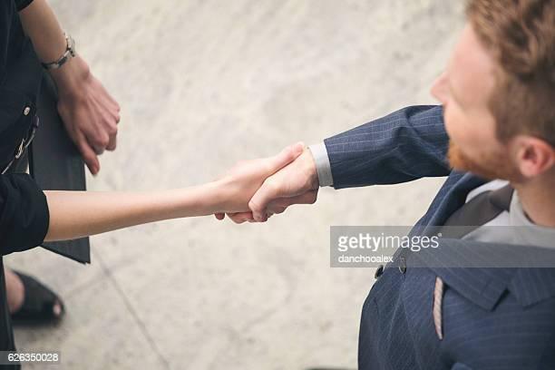 Businessman and businesswoman hand shake overhead shot