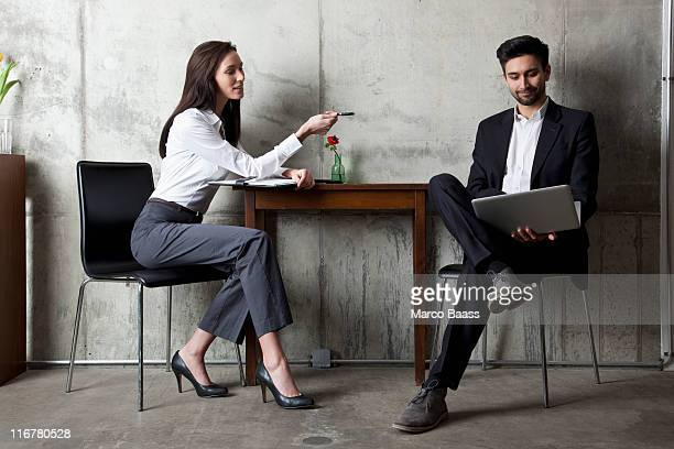 A businessman and businesswoman having a meeting in a modern office