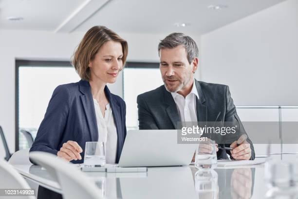 businessman and businesswoman having a meeting in office with laptop - rat stock-fotos und bilder