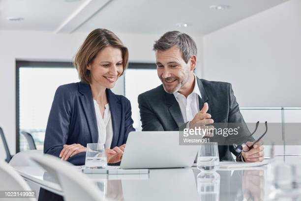 businessman and businesswoman having a meeting in office with laptop - two people stock pictures, royalty-free photos & images