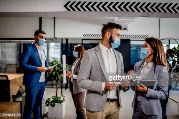 homme d'affaires et femme d'affaires ayant une réunion portant des masques de visage - tenue d'affaires photos et images de collection