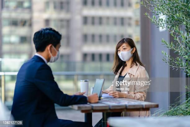 病気予防のための保護フェイスマスク付き屋外カフェでビジネスミーティングを持つビジネスマンとビジネスウーマン - メートル ストックフォトと画像