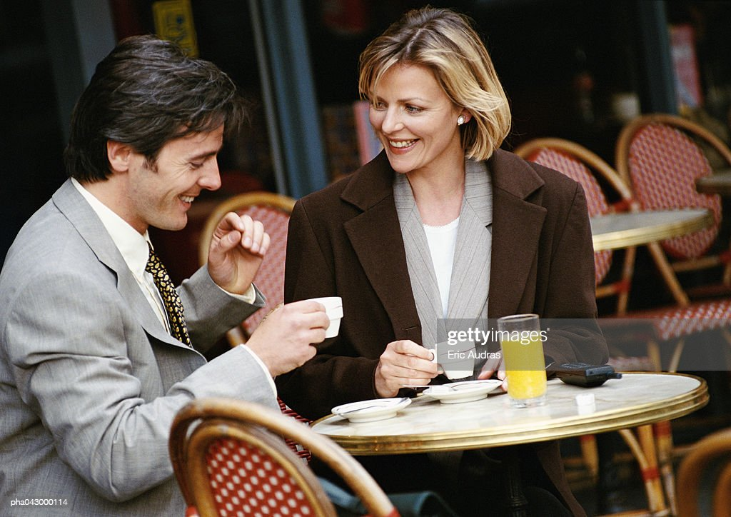 Businessman and businesswoman having coffee at cafe terrace : Stockfoto