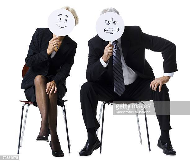 Businessman and businesswoman holding expression masks