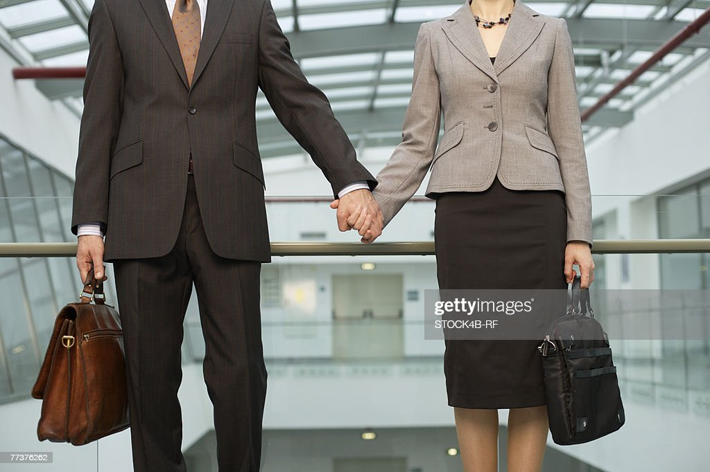 Businessman and businesswoman holding hands : Photo