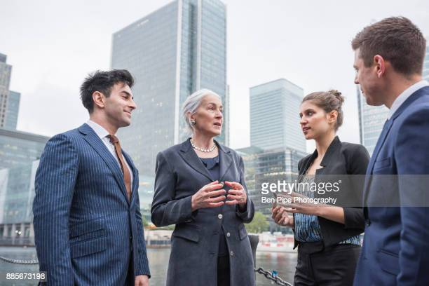Businessman and businesswoman in discussion outdoors, Canary Wharf, London, UK