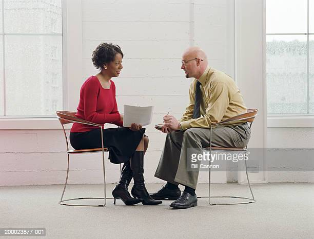 businessman and businesswoman in meeting, discussing paperwork - face to face stock pictures, royalty-free photos & images
