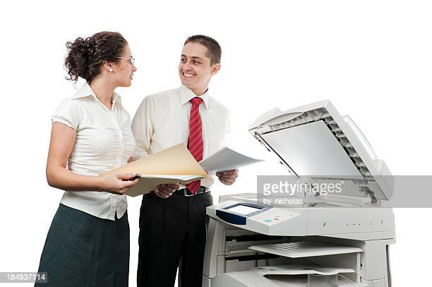 Businessman and businesswoman in office near the printer