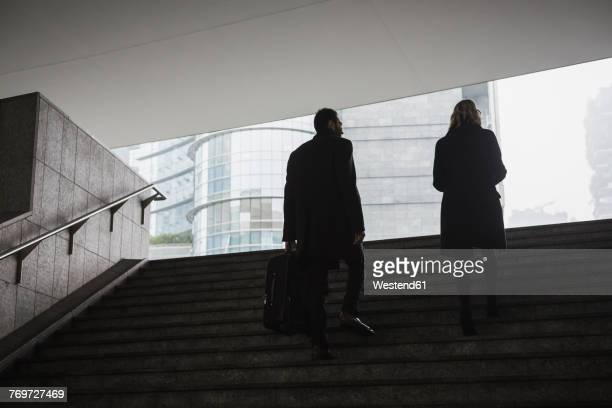 Businessman and businesswoman in the city walking up stairs