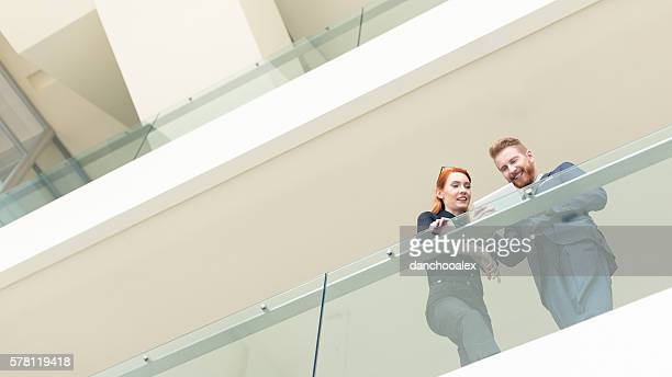 Businessman and businesswoman in the hall using tablet pc
