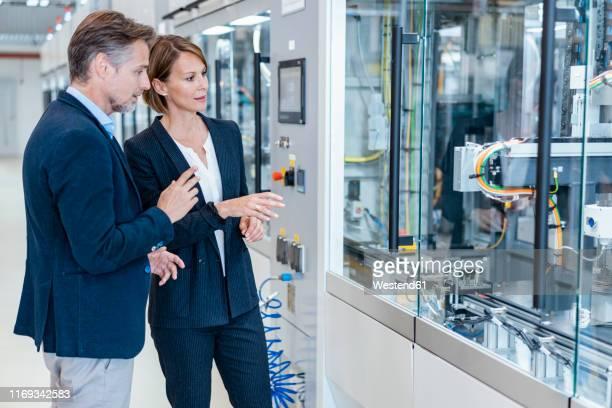 businessman and businesswoman looking at a machine in a modern factory hall - rechnerunterstütztes konstruieren stock-fotos und bilder