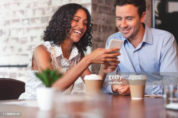 homme d'affaires et femme d'affaires en regardant un téléphone mobile. - collègue photos et images de collection