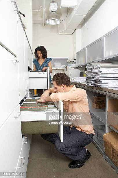 Businessman and businesswoman looking through filing cabinets