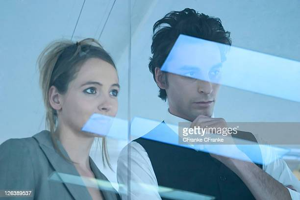 Businessman and businesswoman looking through window
