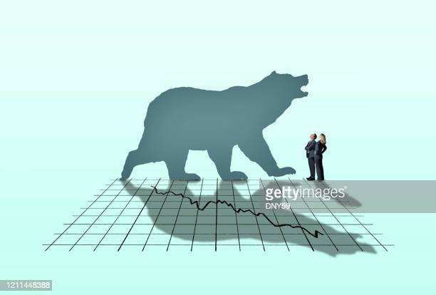 businessman and businesswoman looking up at bear market - bear market stock pictures, royalty-free photos & images