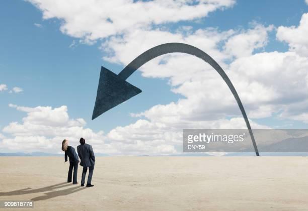 Empresario y empresaria mirando para arriba Flecha entrante