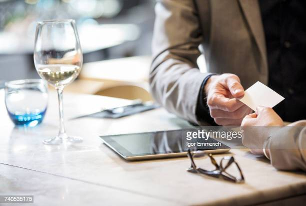 businessman and businesswoman making introductions at lunch in restaurant - business cards stock photos and pictures