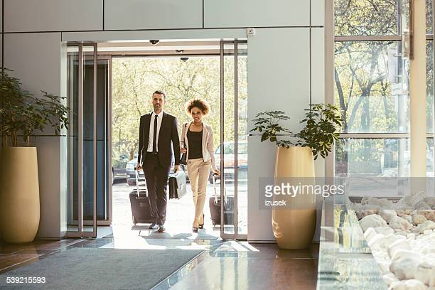 businessman and businesswoman on business travel - hotel stock pictures, royalty-free photos & images