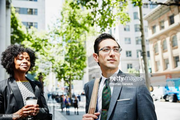 Businessman and businesswoman on downtown city sidewalk