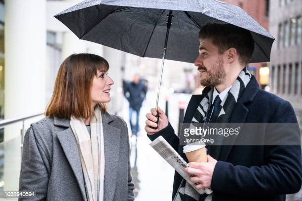 businessman and businesswoman outside in the rain under umbrella - charming stock pictures, royalty-free photos & images
