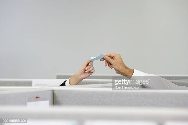 businessman and businesswoman passing note over cubicle wall - 手渡す ストックフォトと画像