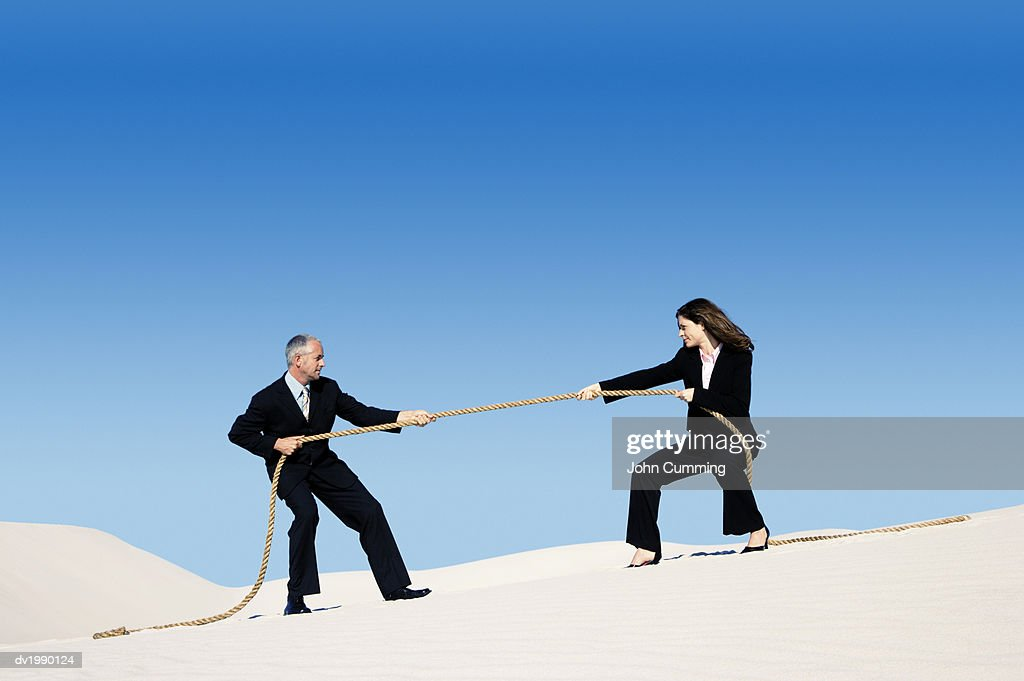 Businessman and Businesswoman Playing Tug of War in a Desert : Stock Photo
